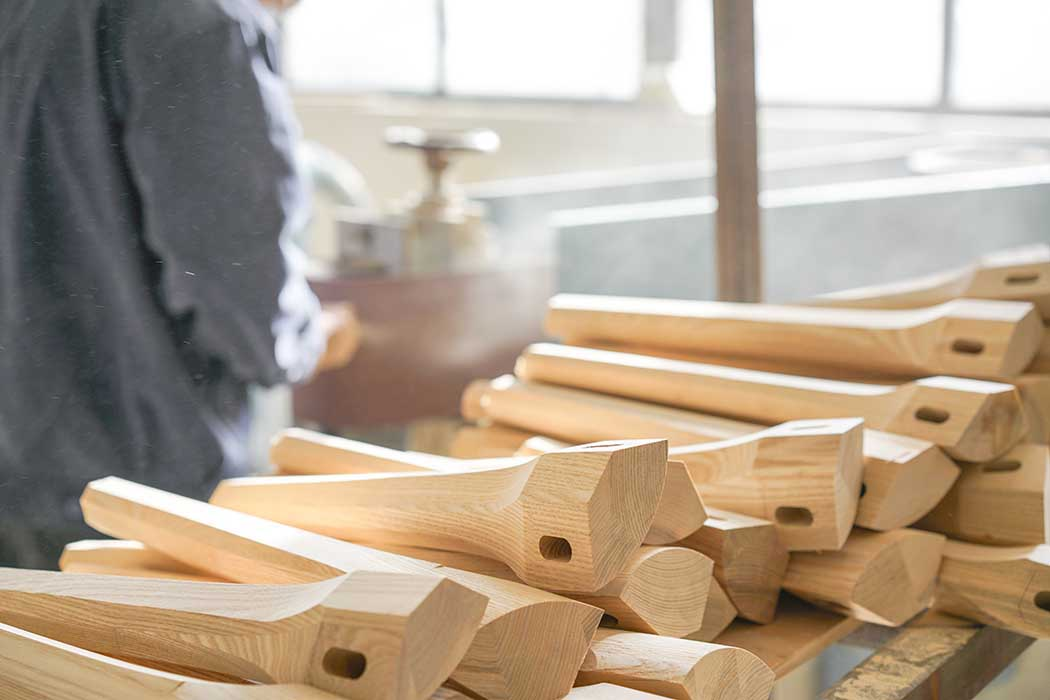 Foto de varias patas de muebles en proceso de fabricación, con una persona en segundo plano, para ilustrar la página de Carpinteros en Santiago de Compostela