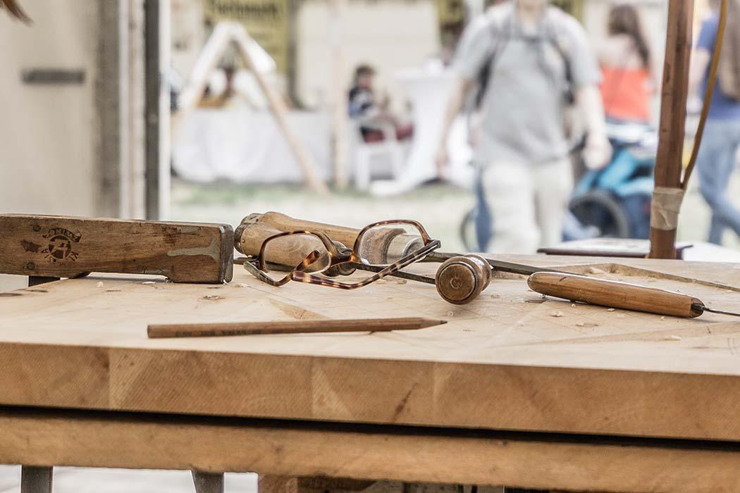 Imagen de una mesa de carpintero con algunos útiles encima en primer plano, y personas en el taller al fondo, desenfocadas. Se utiliza para ilustrar la página de carpinteros en Santiago de Compostela